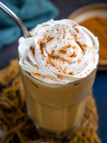 This Starbucks Copycat Iced Pumpkin Spice Latte takes 5 minutes to come together at a fraction of the cost. It's made using real pumpkin and is perfect to sip on warmer fall and autumn days.
