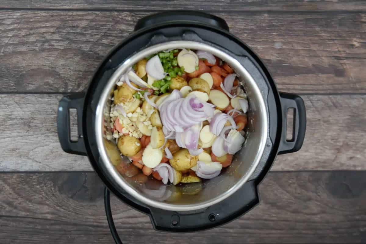 Onion, baby potatoes, carrots, celery and garlic added in the pot.