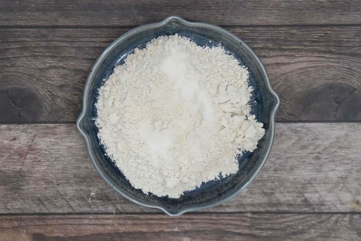 Jowar flour and salt added in a flat bowl.