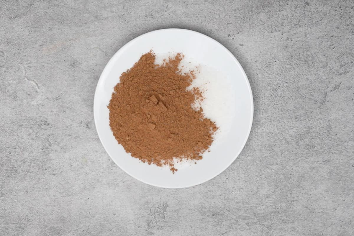 Castor sugar and pumpkin pie spice mixed in a shallow plate.
