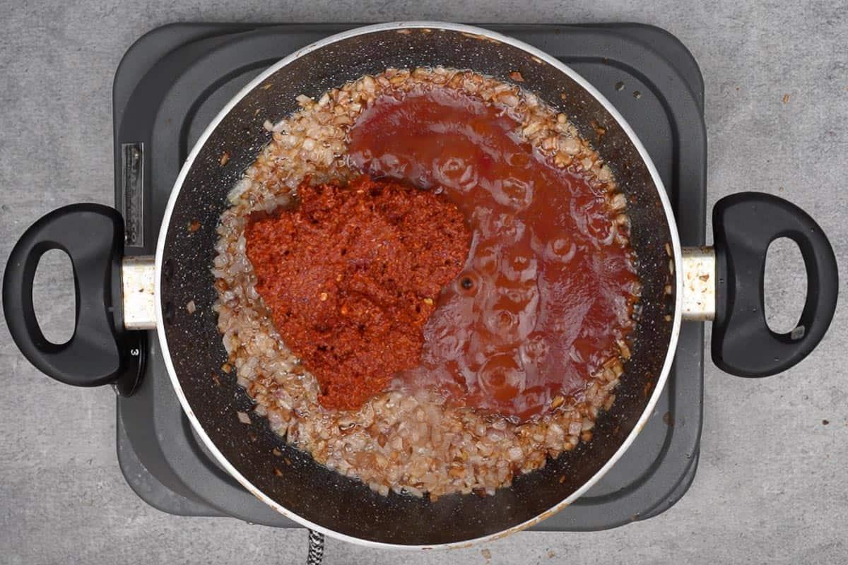 Tomato puree and vindaloo paste added to the pan.