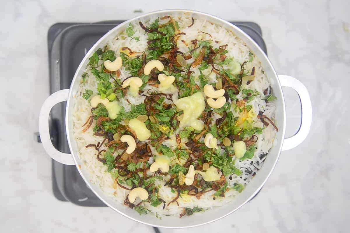 Coriander leaves, mint leaves, saffron soaked in milk, fried onion, fried cashew nuts and raisins sprinkled over rice.