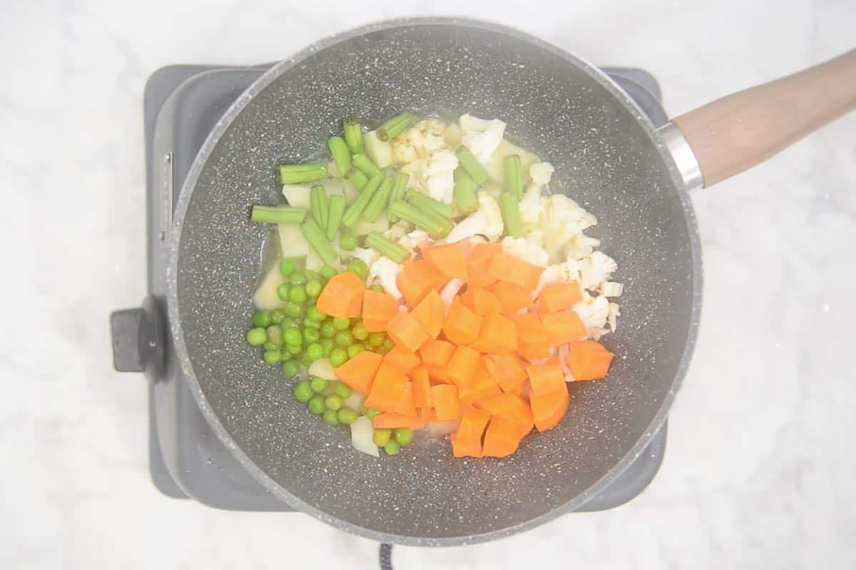 Vegetables frying on high heat.