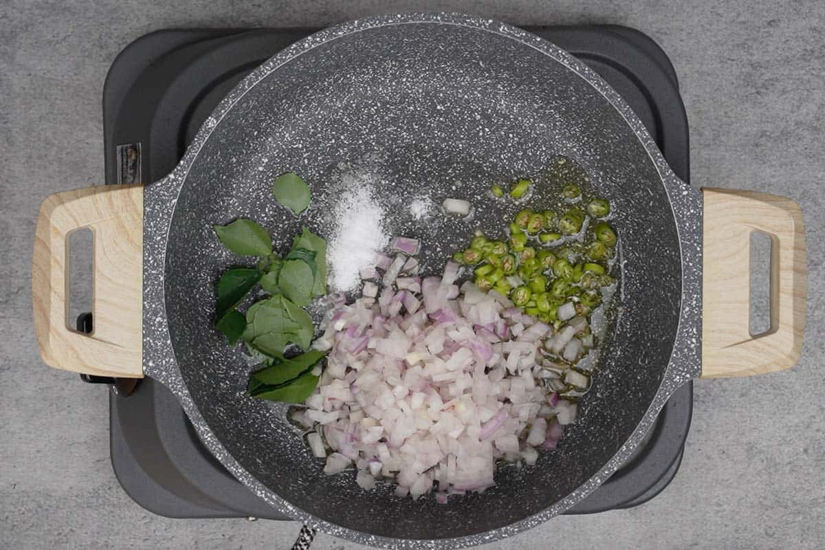 Green chilies, onions and curry leaves added to the pan.