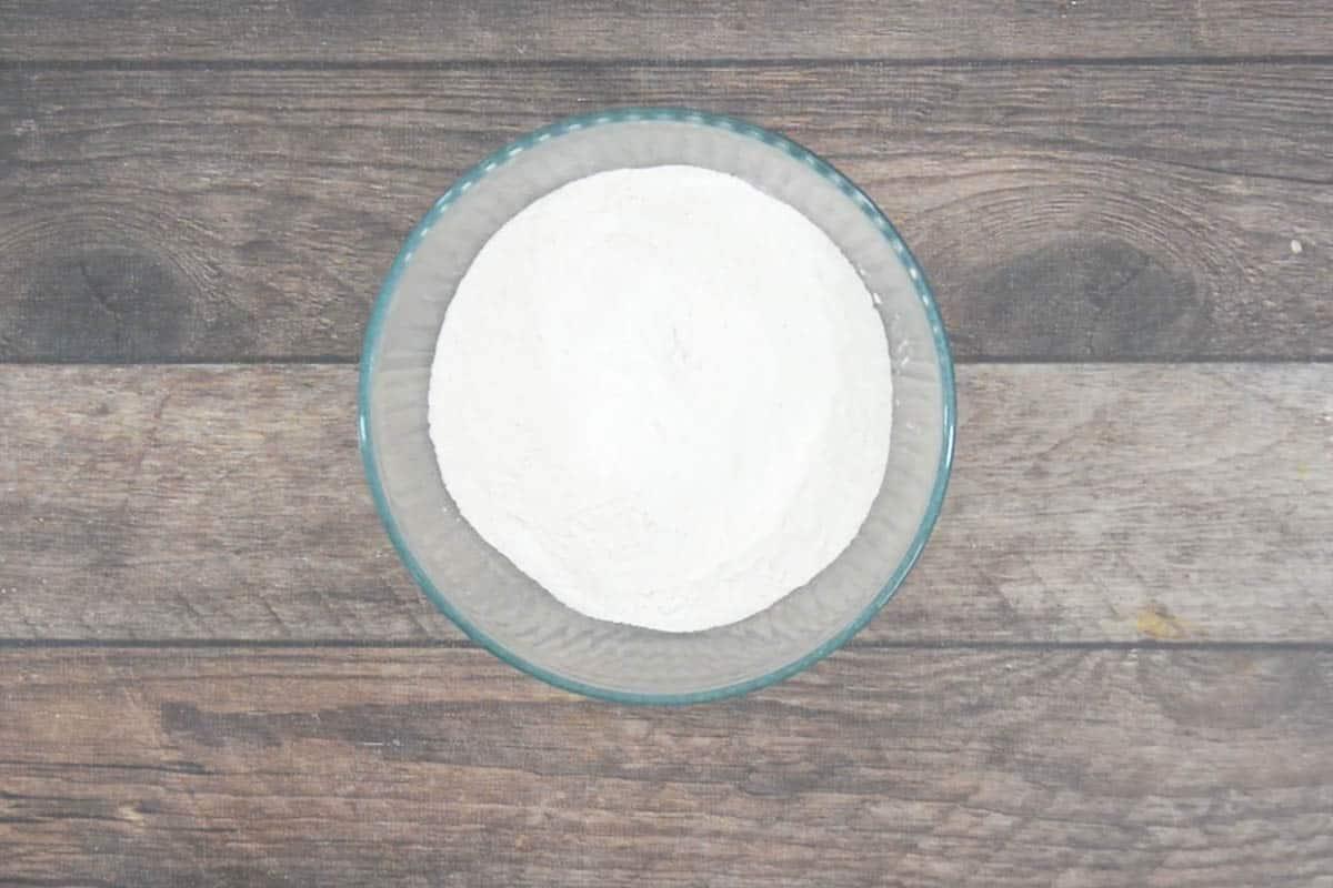 flour, baking soda, baking powder, and salt added to a bowl.