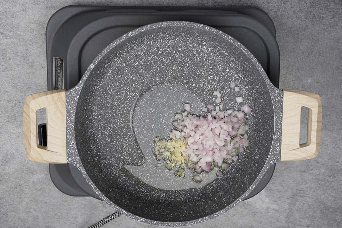 Onions and garlic added to hot oil in a pan.