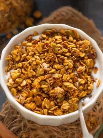 Make this healthy and super easy homemade Pumpkin Spice Granola at home in under 30 minutes using 8 ingredients. It's super crunchy and loaded with fall flavors.