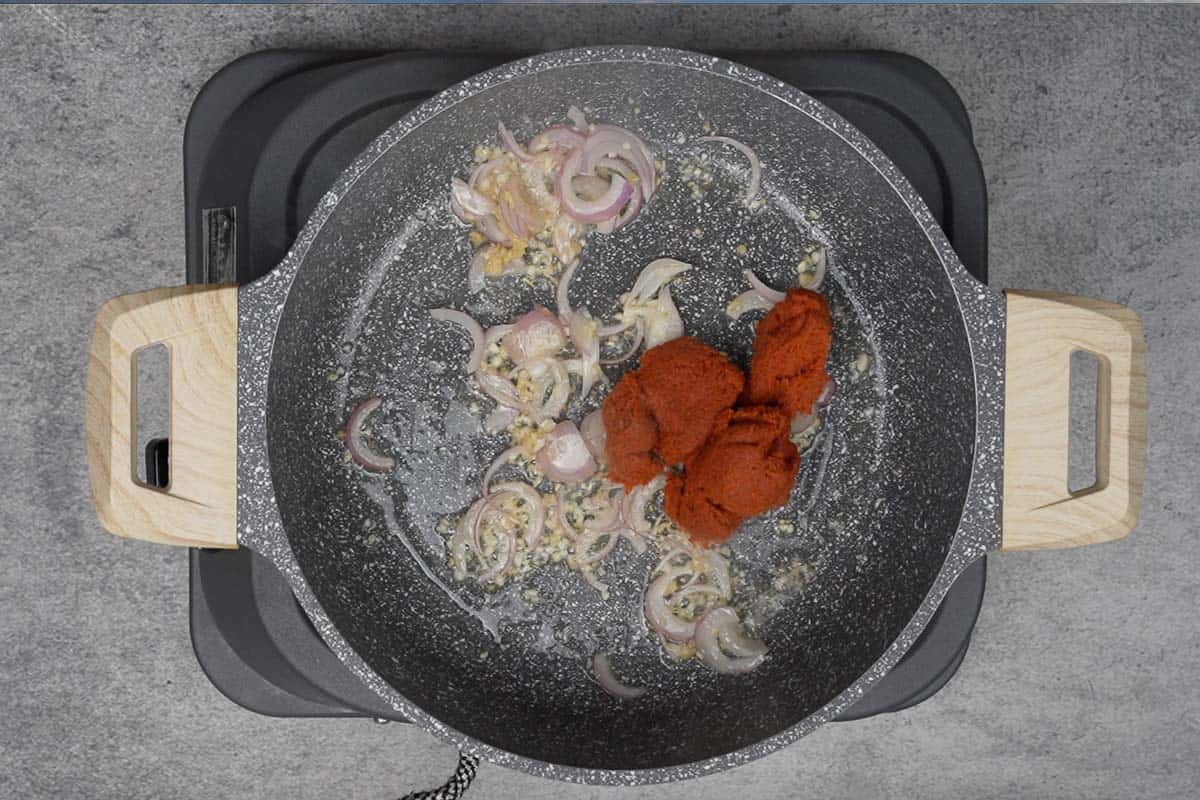 Thai red curry paste added to the pan.