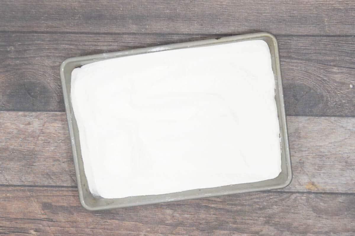 Cake flour spread on a baking tray.