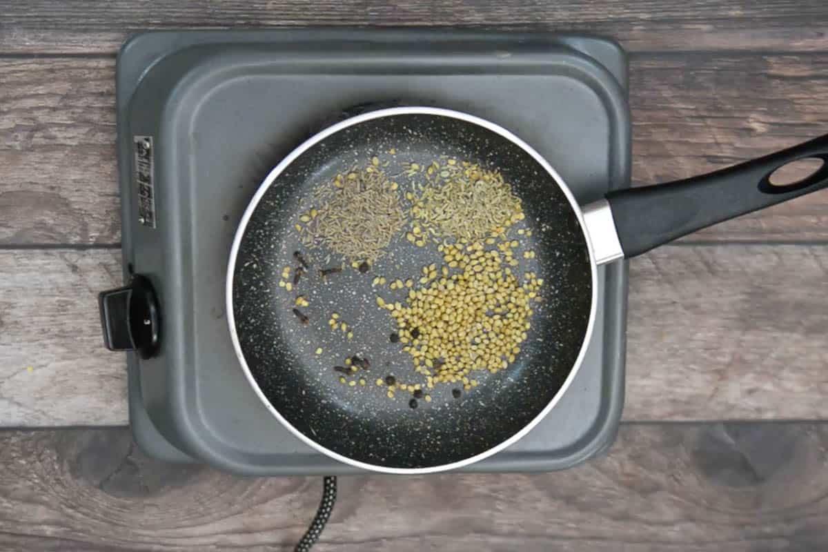 Coriander seeds, fennel seeds, cumin seeds, fenugreek seeds cloves and black peppercorn roasting in a pan.