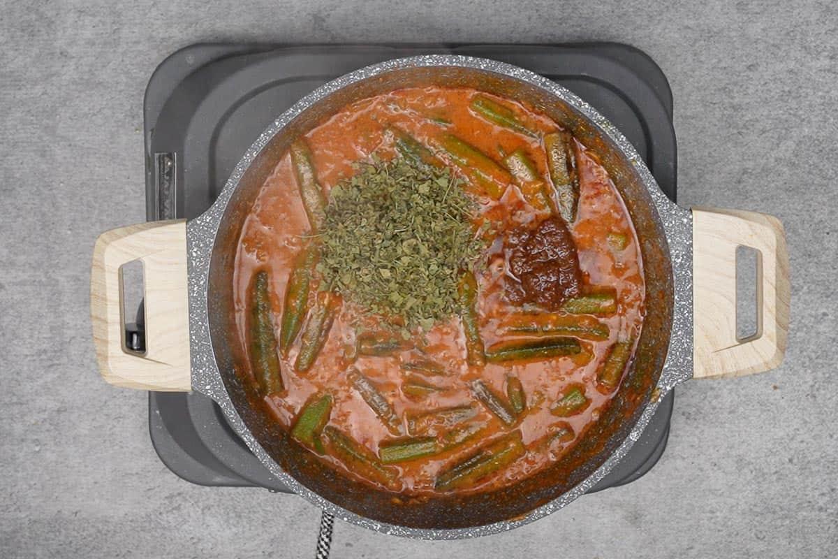 Mango pickle and kasuri methi added to the pan.
