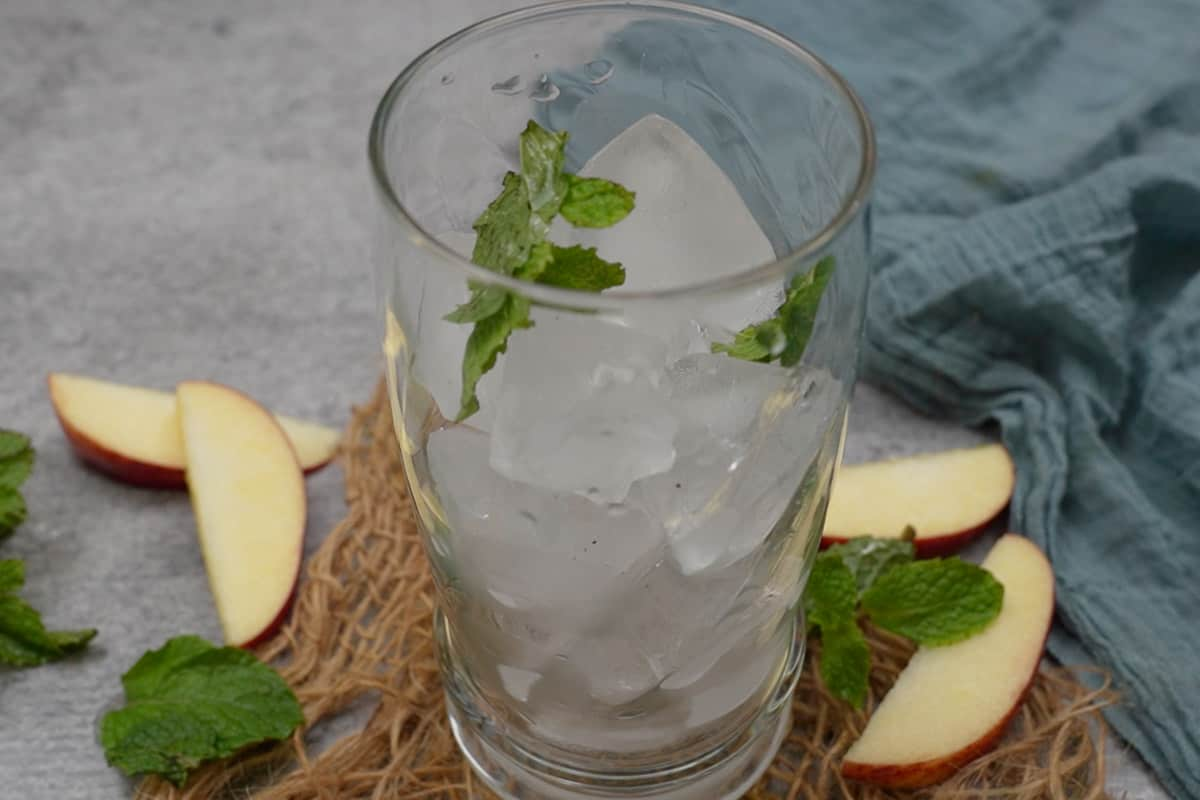 Mint leaves and ice cubes added to a tall glass.