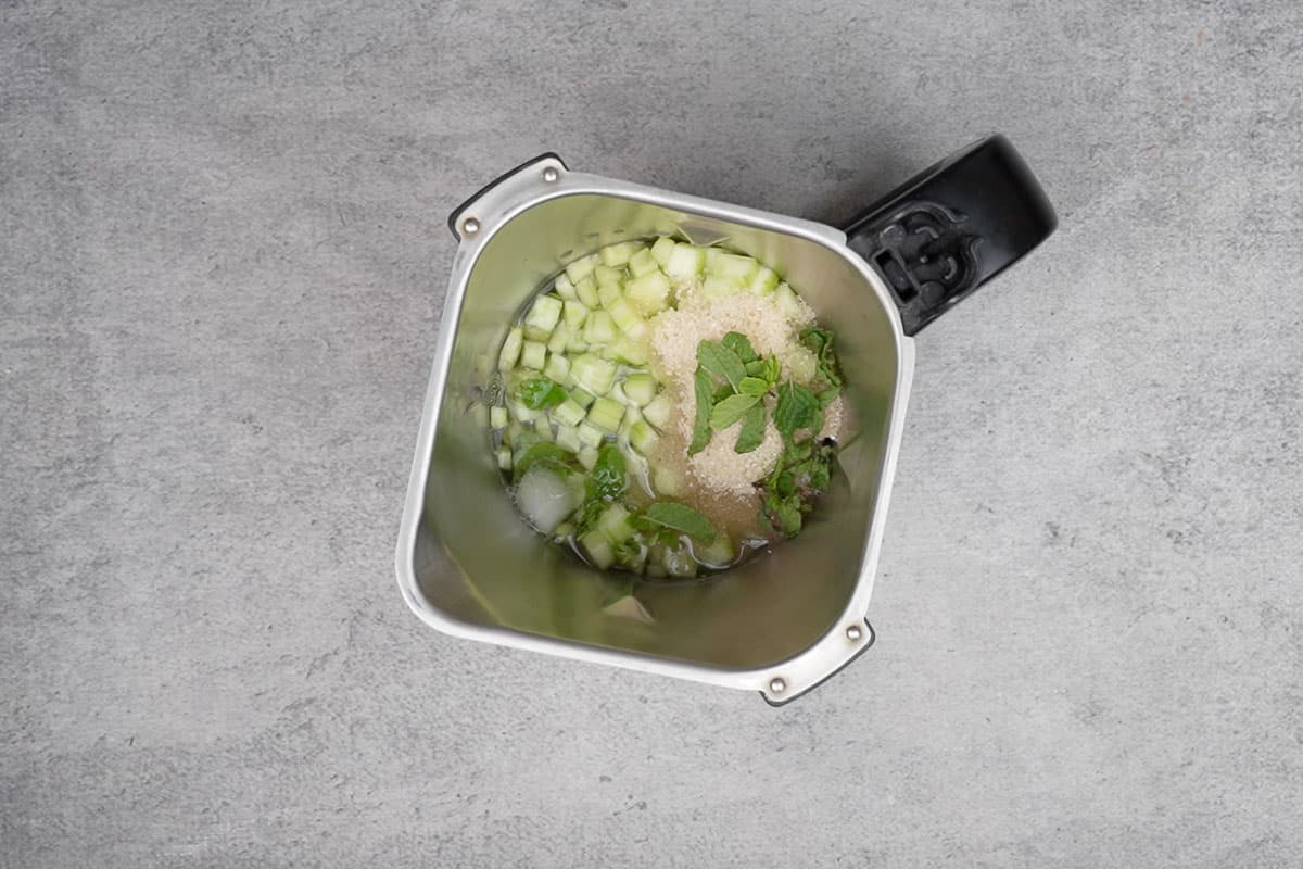 Chopped cucumber, sugar, mint leaves and 1 cup added to a blender.blender.