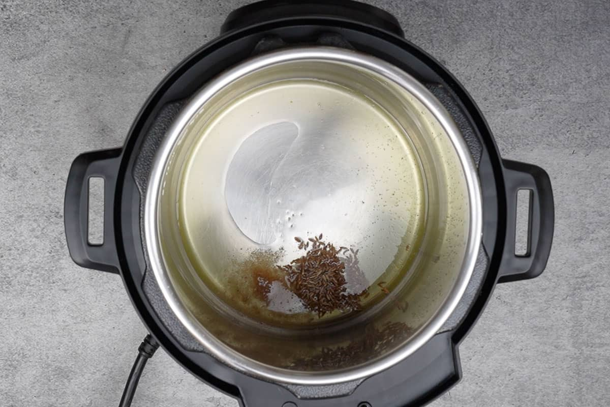 Cumin seeds and asafetida added to hot ghee in instant pot.