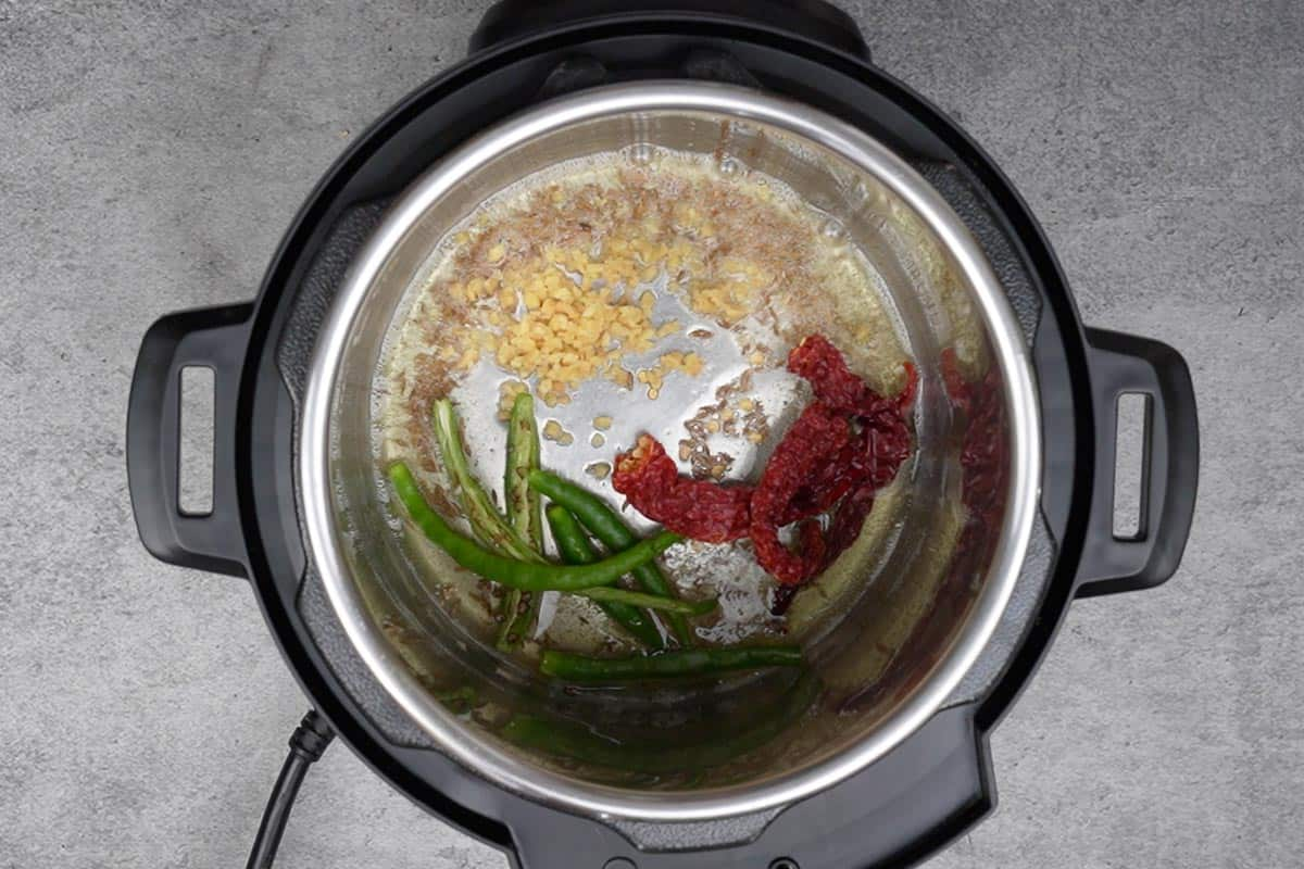 Whole dry red chilies, green chilies and ginger added to the pot.