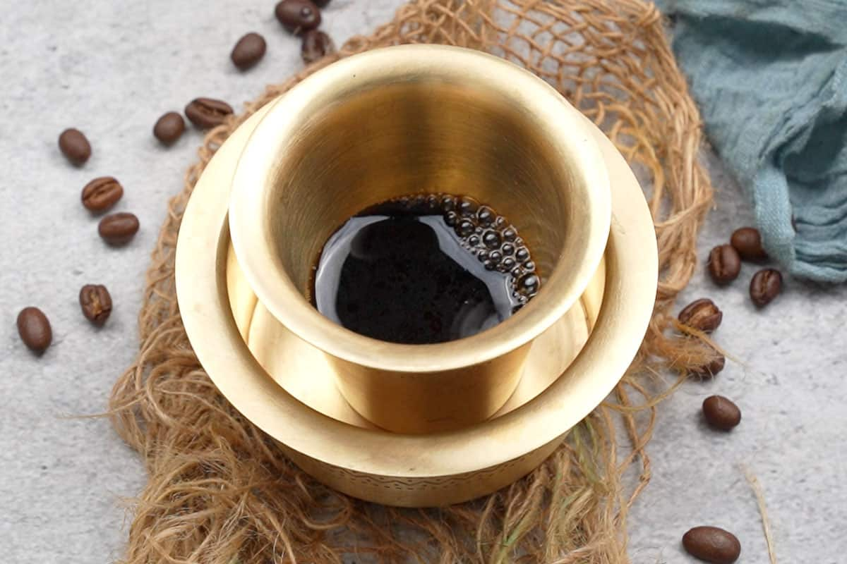 Coffee decoction added to a tumbler.