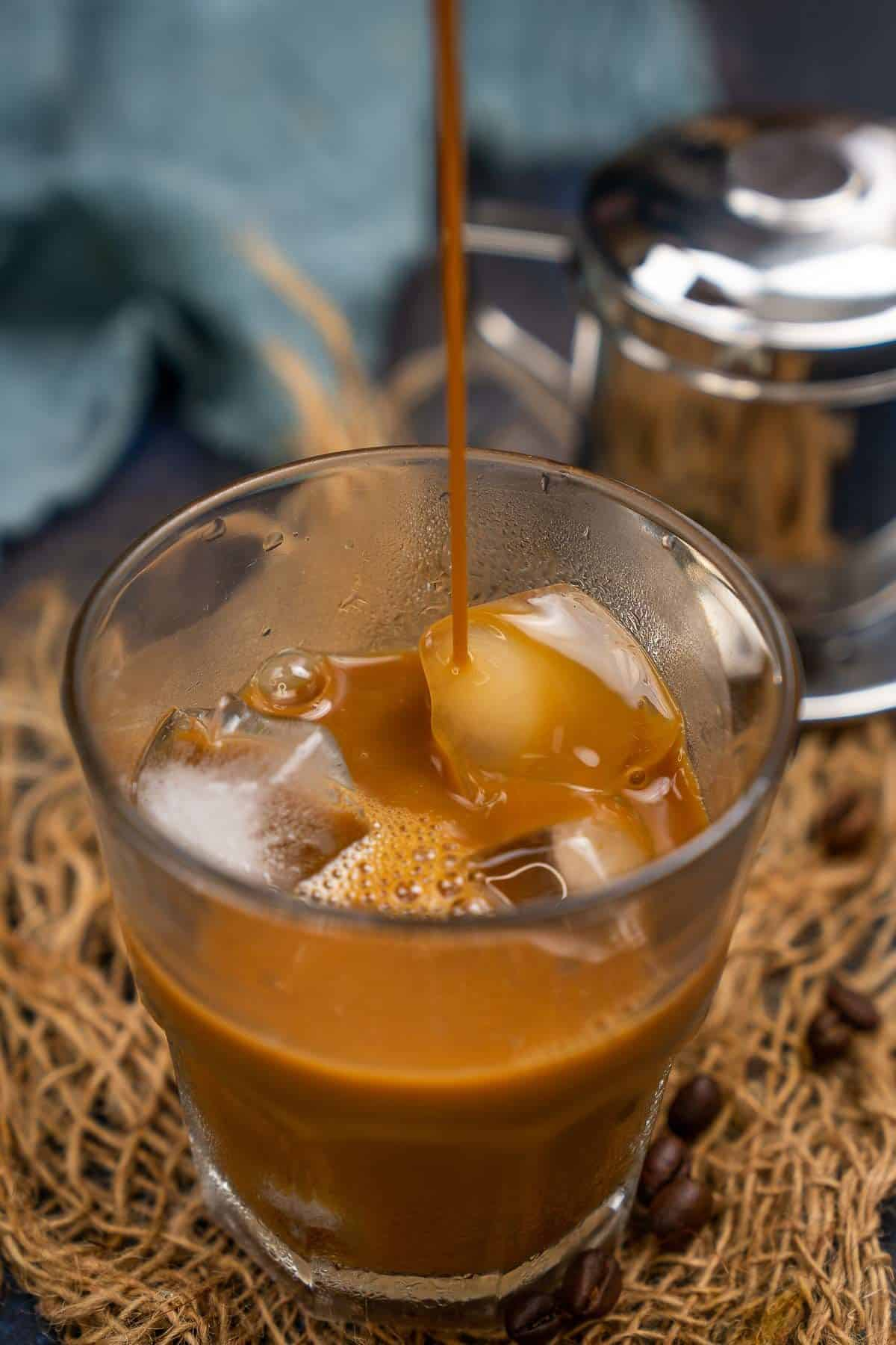 Vietnamese coffee pouring over ice to make Vietnamese iced coffee.