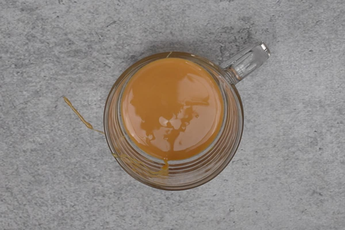 Condensed milk added to a cup.