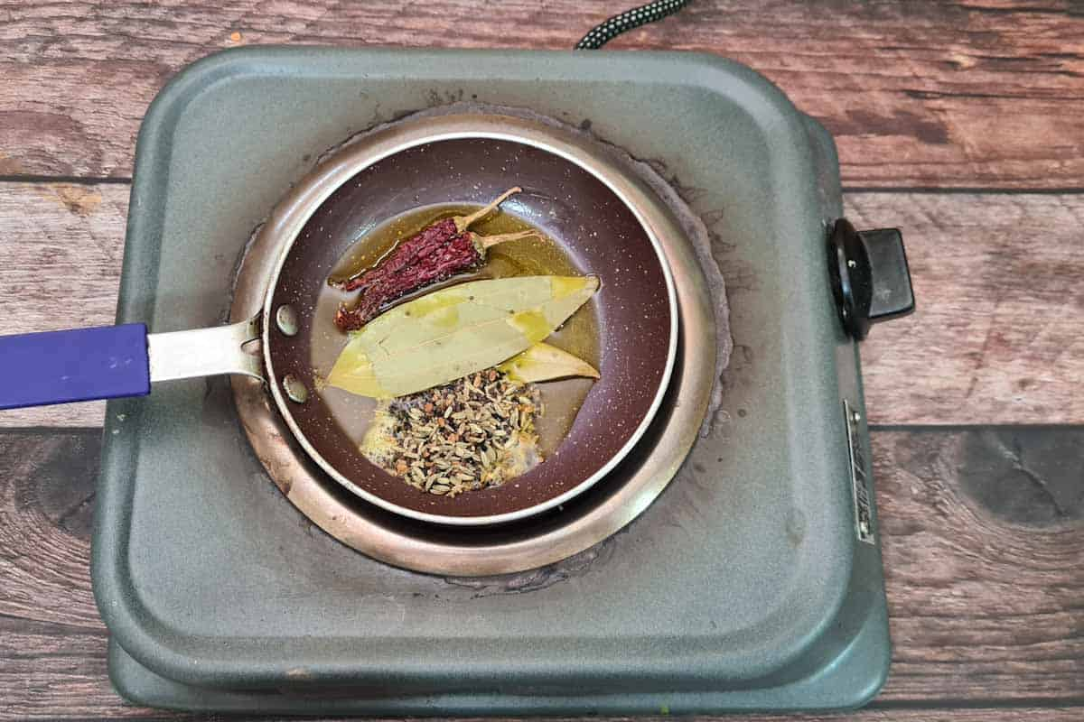 Bay leaves, dry red chilies, panch phoran added to the pan.