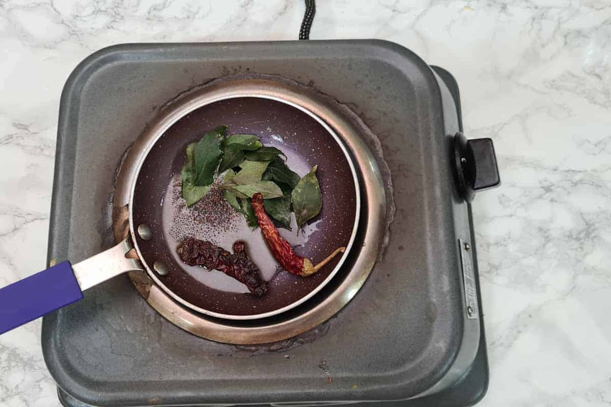 Mustard seeds, curry leaves and dry red chilies added to the pan.