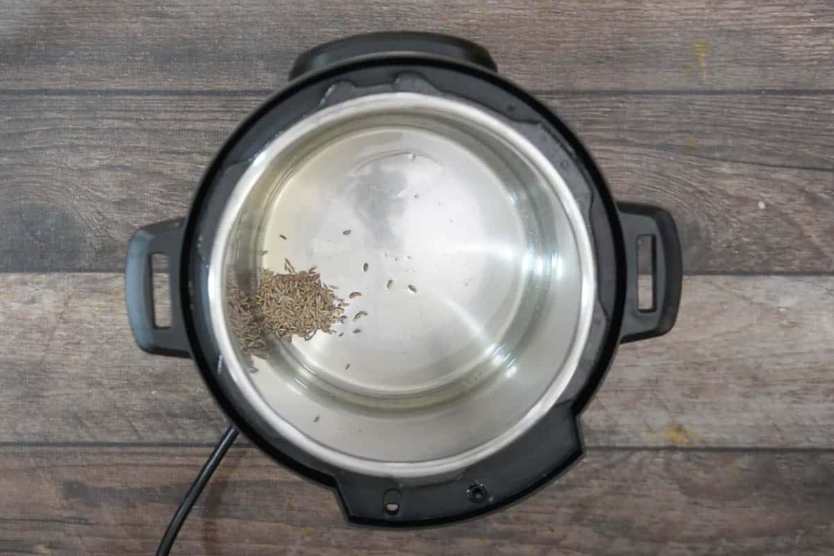 Cumin seeds added to the pot.
