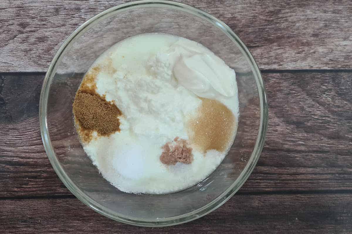 Yogurt, cream, sugar, black salt, regular salt, and roasted cumin powder added to a bowl .
