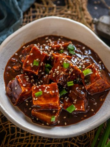 Korean Gochujang Tofu is a vegan and gluten-free dish where tofu is baked or fried until crisp from outside and then mixed with a savory spicy sauce. Make this easy and delicious dish at home instead of an expensive take-out.