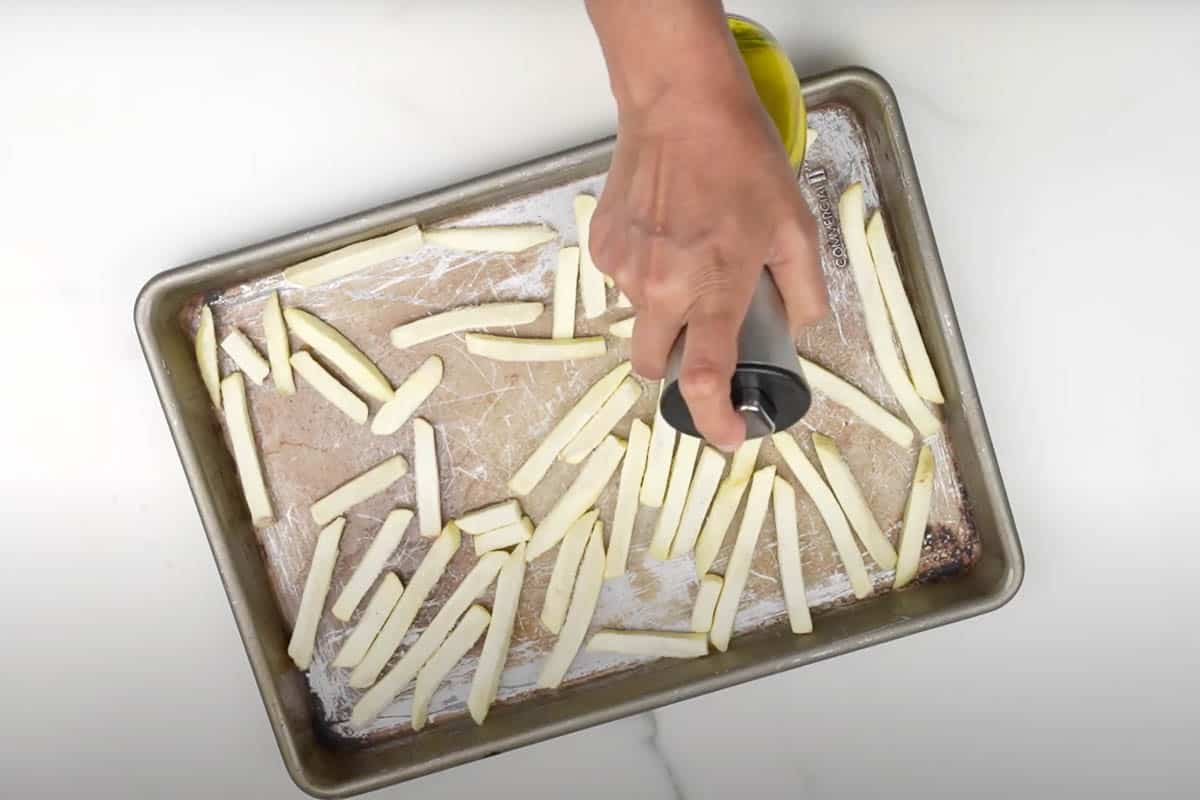 Frozen french fries being sprayed with oil.