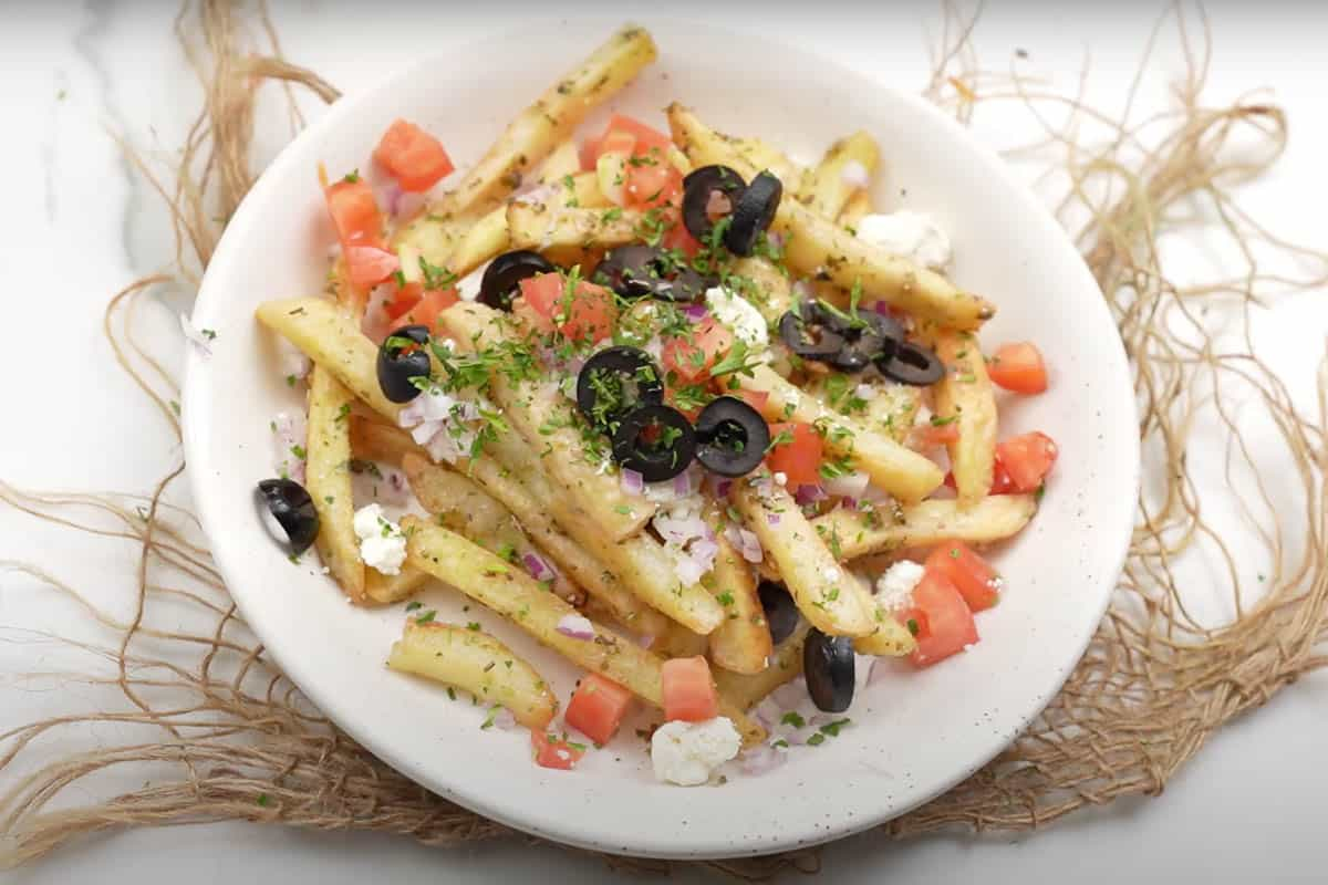 Ready Greek fries topped with onion, tomato, olives, parsley and Feta cheese.