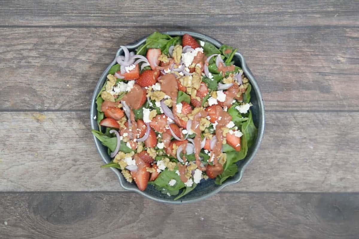 Ready strawberry walnut salad drizzled with dressing.