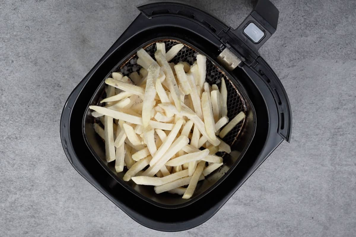 Frozen fries in the basket of the air fryer.