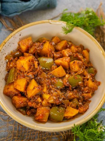 This simple and delicious Punjabi style aloo shimla mirch (aloo capsicum fry) is a delight to eat with roti or paratha. Serve it for lunch or dinner or pack for lunch boxes.