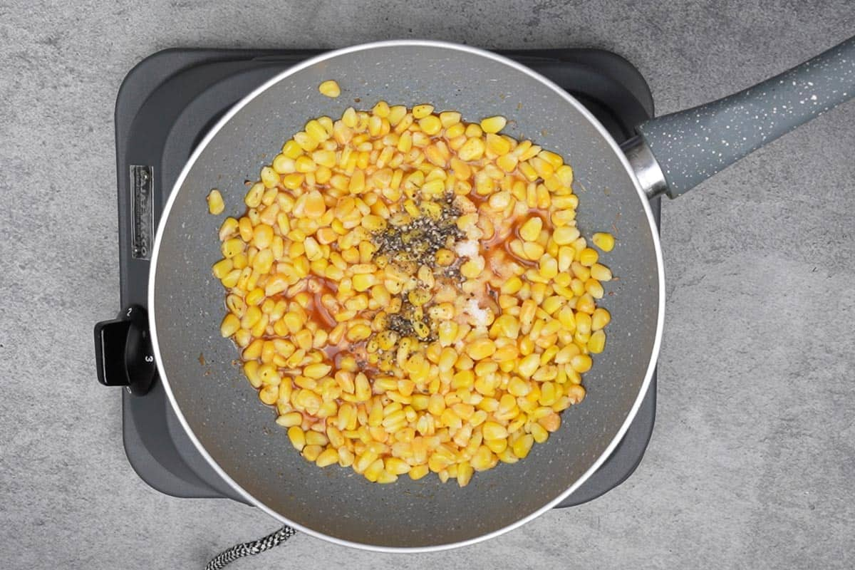 Corn, salt and pepper added to the pan.