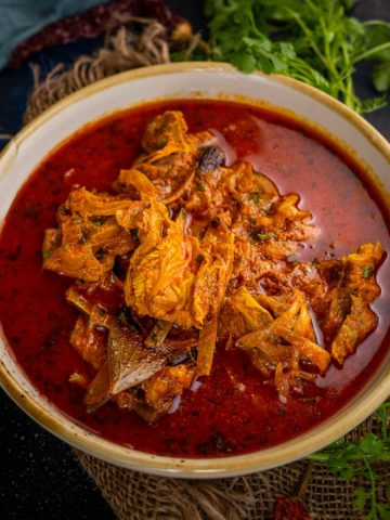 Laal maas is a traditional Rajasthani mutton (goat meat) curry that is fiery hot and deep red in color. Make it at home in an instant pot or a traditional pressure cooker using my authentic recipe.