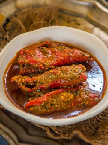 This hot, spicy, and tangy lal mirch ka achar or stuffed red chili pickle is my mom's signature recipe. It is a perfect spicy condiment to serve with your everyday Indian meals. Here is how to make it.