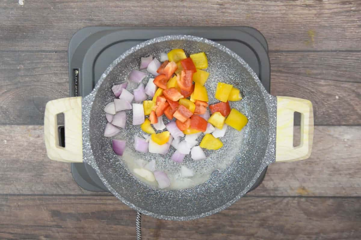 Onion and bell peppers added to a skillet.