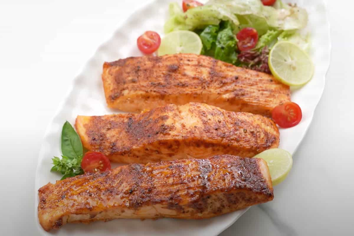 Ready air fryer salmon served on a plate.