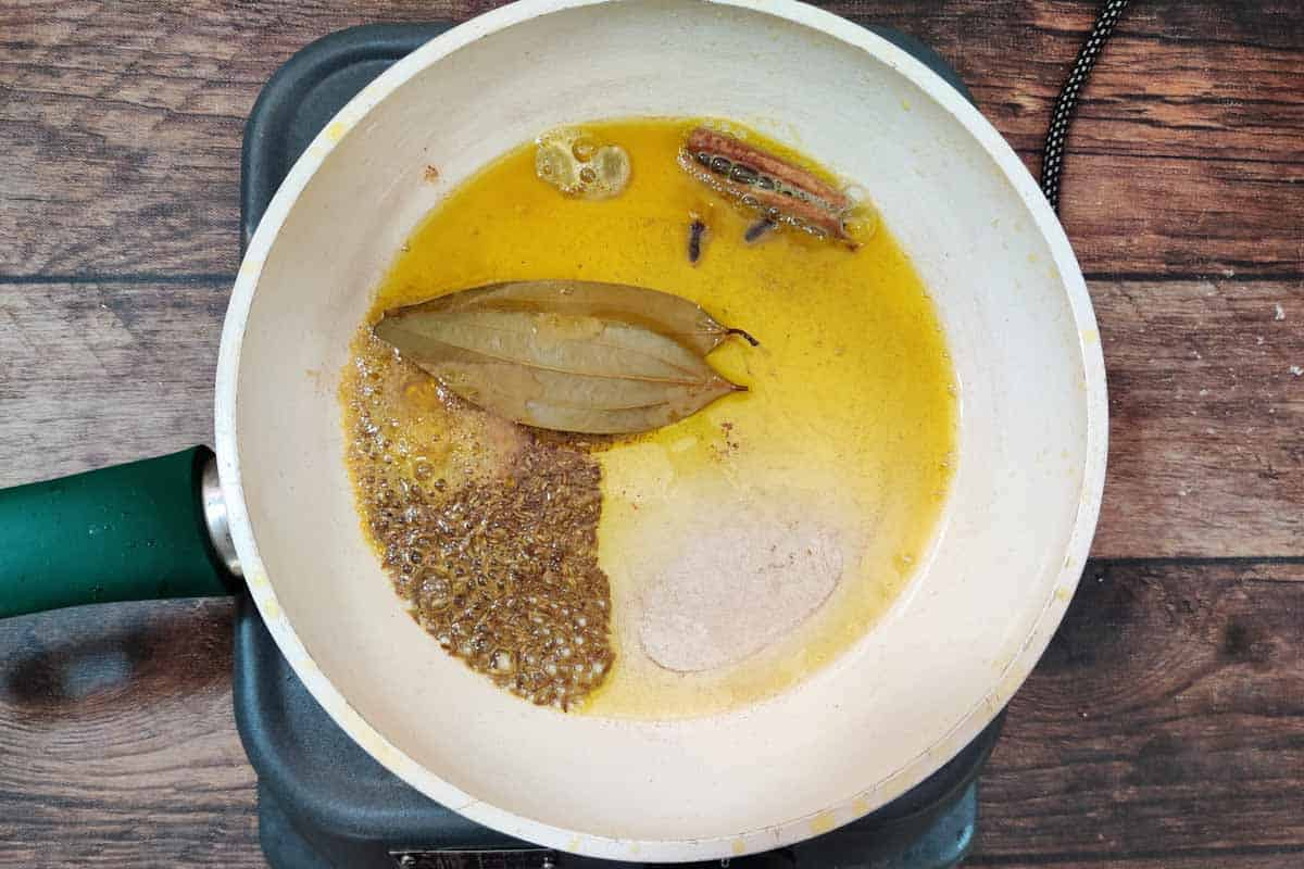 Cumin seeds and whole spices added in hot oil.
