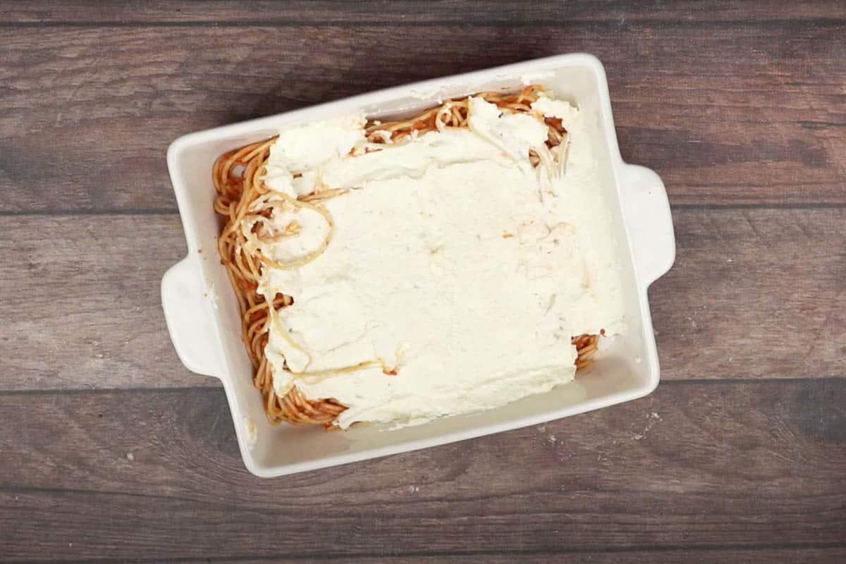 Cheese mixture spread over spaghetti.