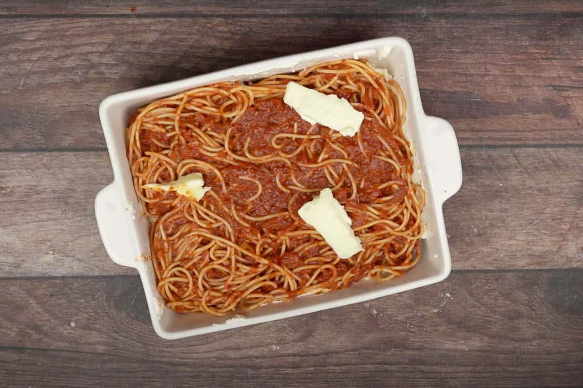 Remaining spaghetti spread over the cheese and topped with the remaining butter.
