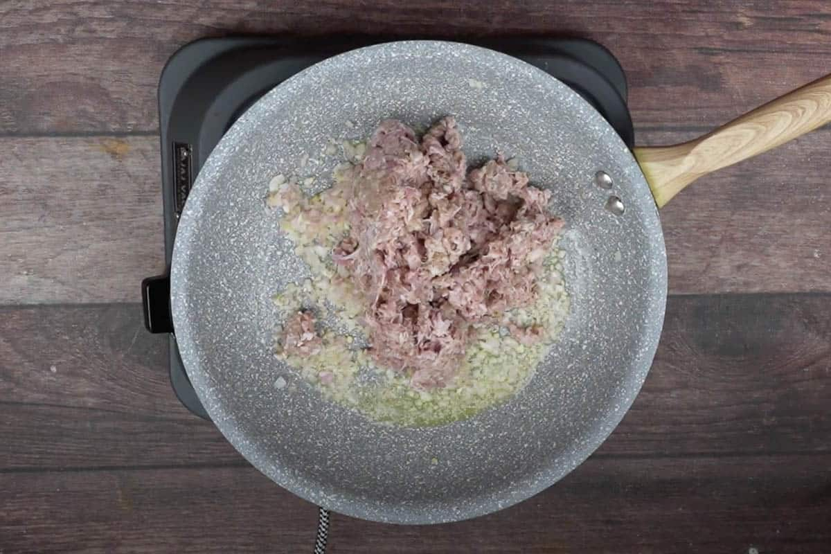 Ground beef added to the skillet.