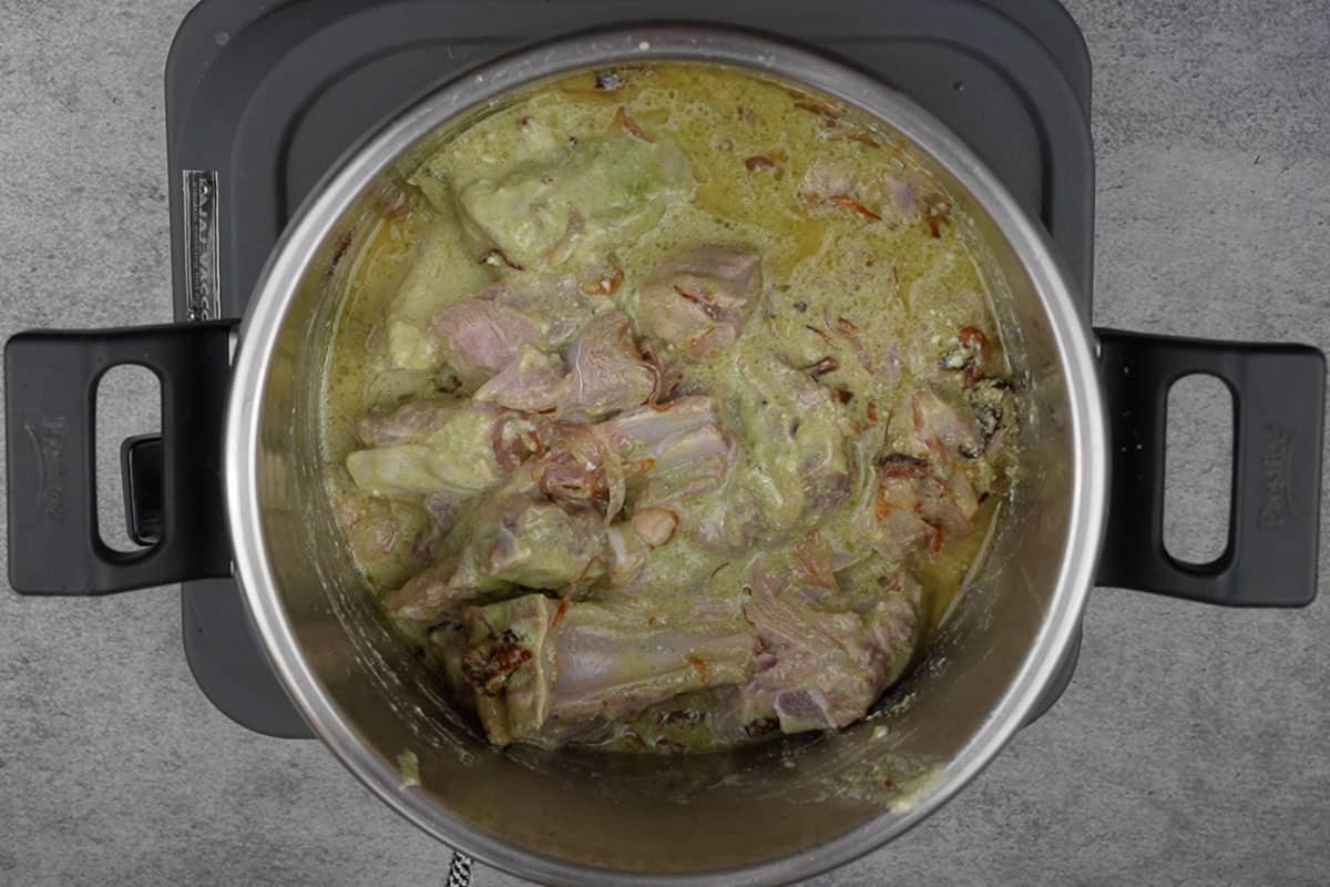 Marinated mutton along with the marinade added to the cooker.