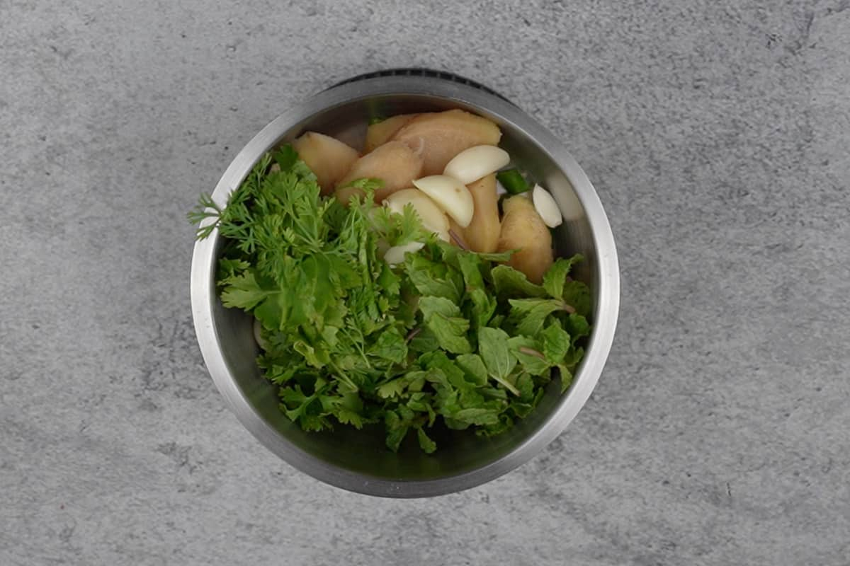 Green chilies, ginger, garlic, cilantro, mint and some water added to a blender.