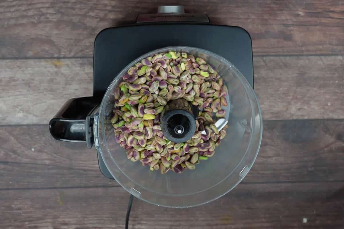 Roasted pistachios added to a food processor.