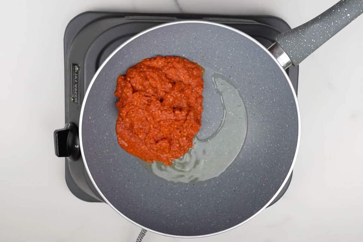 Chili paste added to the pan with vegetable oil.
