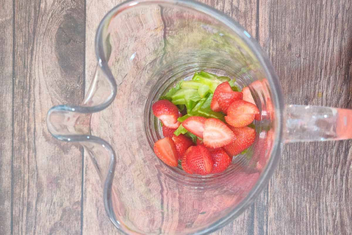 Sliced starfruit, halved strawberries added to a large pitcher.