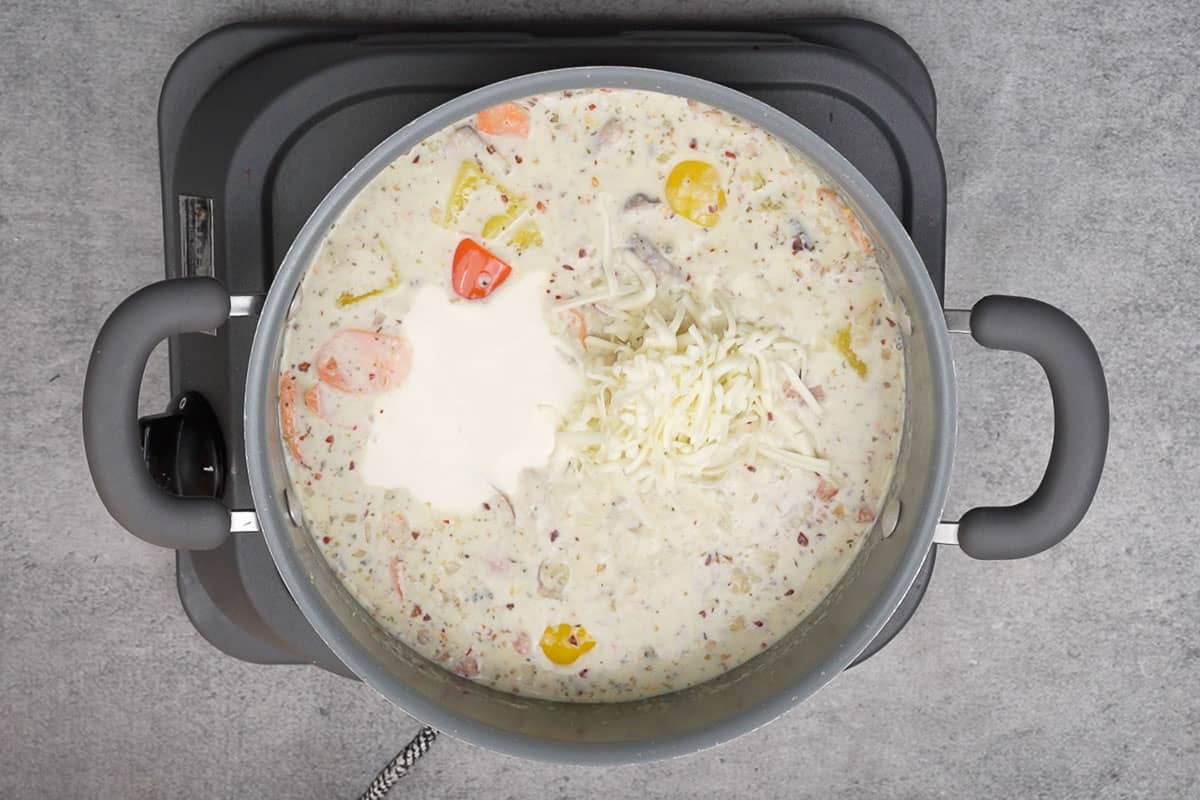 Heavy cream and cheddar cheese added to the pan.