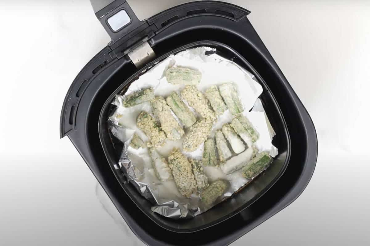 Okra lined in the basket of the air fryer.