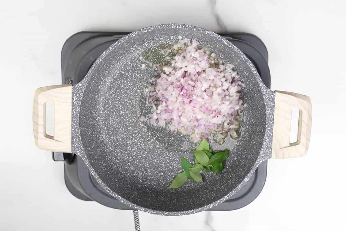 Curry leaves and chopped onions added to the pan.