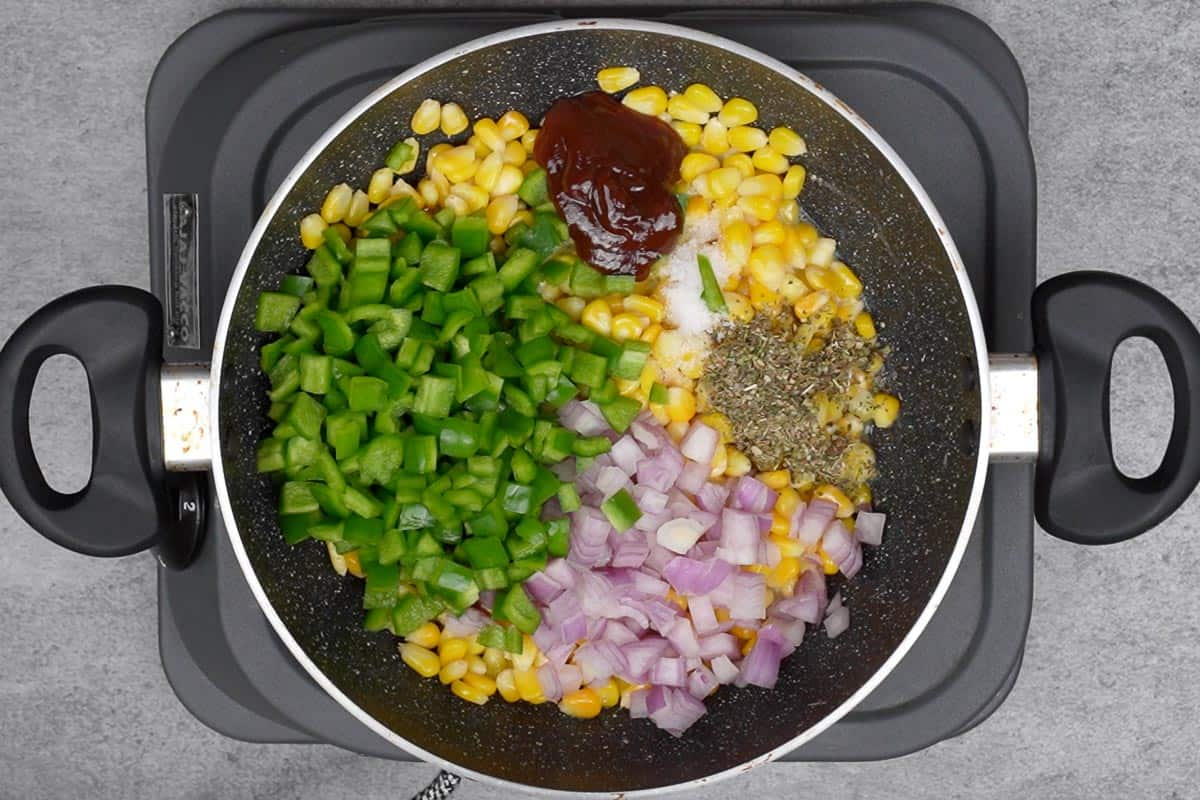 Italian seasoning, salt, onions, bell peppers, and ketchup added to the pan.